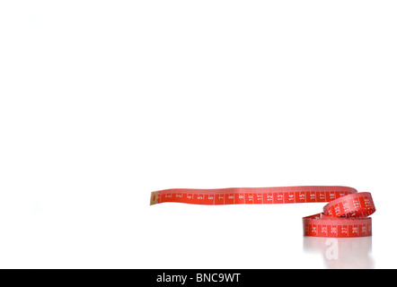 A coiled red metric measuring tape - Stock Photo
