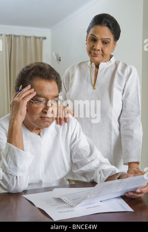 Man looking at a bill with a woman standing beside him - Stock Photo
