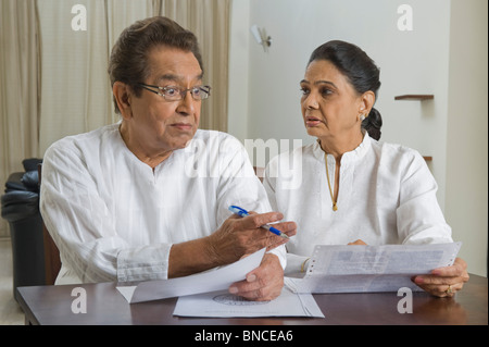 Man looking surprised at a bill held by a woman - Stock Photo