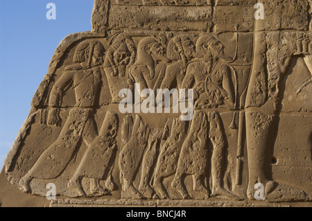 Temple of Ramses III. Relief depicting prisoners of war at the feet of Pharaoh, represented a larger size. - Stock Photo