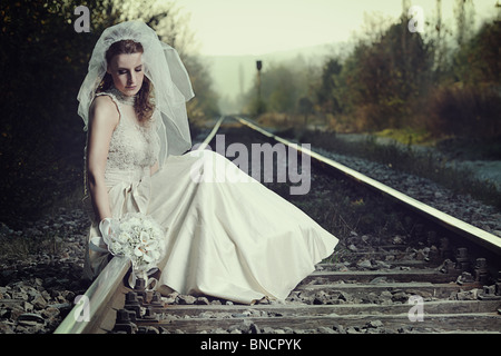 A view of a disappointed bride on a railway - Stock Photo