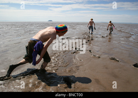 Group of lads trudging through mud during low tide, Weston-Super-Mare, UK - Stock Photo