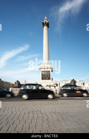 Nelson's Column and black taxi cabs at Trafalgar Square, London, England, UK - Stock Photo