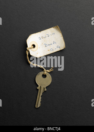 Old key with label with the witing 'Studio Door B-9' - Stock Photo