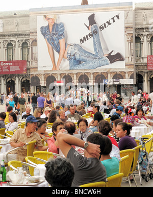 St Marks Square in Venice (Piazza San Marco) on  a crowded evening with a huge advertising billboard behind - Stock Photo
