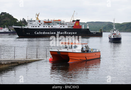 A ferry entering Oban with two smaller boats in front - Stock Photo