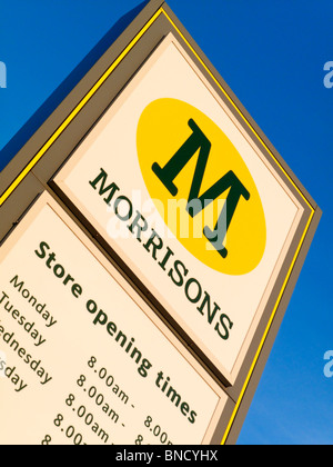 Morrisons supermarket sign with store opening times displayed below the company logo - Stock Photo