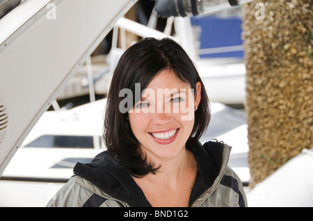Casual portrait of a happy brown eyed brunette young woman on the back of a boat in Seattle's Bell Harbor Marina. - Stock Photo