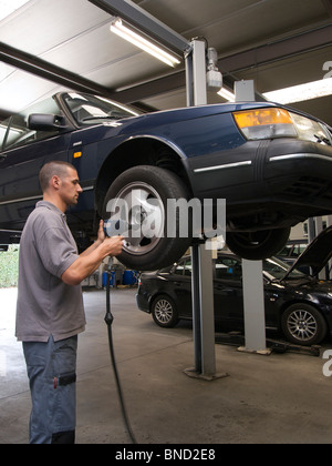 car mechanic working on a wheel of a Saab convertible inside a tidy workshop Turnhout Belgium - Stock Photo