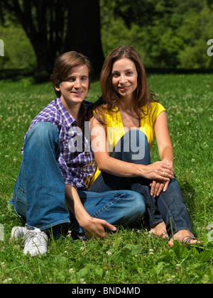 Young happy smiling couple in their early thirties sitting on grass in a park - Stock Photo