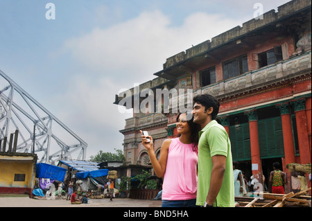 Couple standing in a city with a bridge in the background, Howrah Bridge, Kolkata, West Bengal, India - Stock Photo
