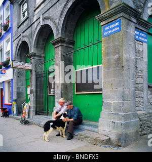 Two elderly men with a Border Collie dog sitting at the Square, Westport, County Mayo, Republic of Ireland - Stock Photo