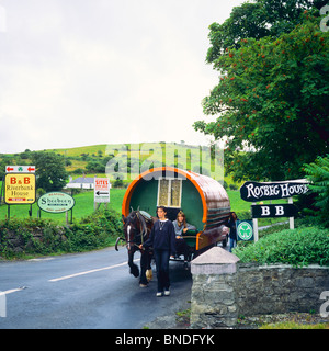 Girl leading horse drawn gypsy caravan on country road, County Mayo, Republic of Ireland - Stock Photo