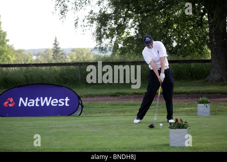 Golf action woman tees off NatWest Island Games 2009 on the Kastelholm Course in Sund on Åland, July 1 2009 - Stock Photo