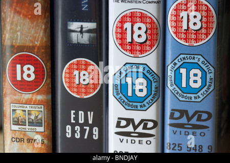 row of dvd video cases showing BBFC and irish film censors office 18 classification notice from the uk - Stock Photo