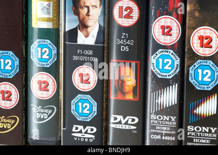 row of dvd video cases showing BBFC and irish film censors office 12 classification notice from the uk - Stock Photo