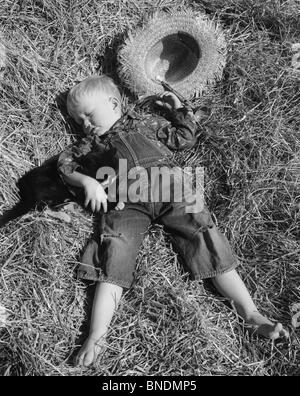 Boy sleeping with cat on hay - Stock Photo
