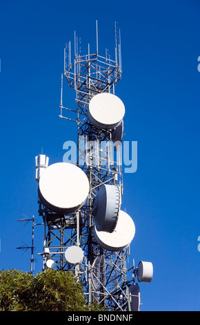 a communication tower silhouetted against blue sky. There are large dishes at the front suitable to add copy or - Stock Photo