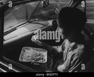 High angle view of a young man eating French fries in a car, 1952 - Stock Photo