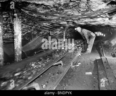 Side profile of a miner standing in the tunnel - Stock Photo