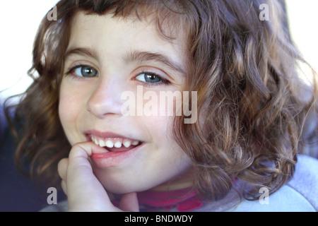little girl smiling shy biting finger blue eyes - Stock Photo