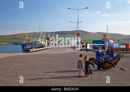 Schoolgirls sitting on bronze sculpture of Fungie the dolphin sculpted by James Bottoms Dingle Peninsula County - Stock Photo