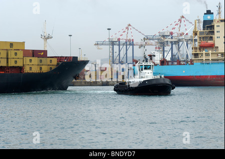 A tug boat pulling a large container ship in Durban Harbor, Durban, Kwazulu Natal, South Africa - Stock Photo