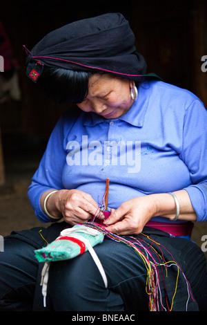 Yao woman sewing in Dazhai Village, Longsheng, Guangxi Province, China - Stock Photo