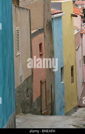 Colourful plaster faced terraced houses line a narrow and steep street in Bosa, Sardinia