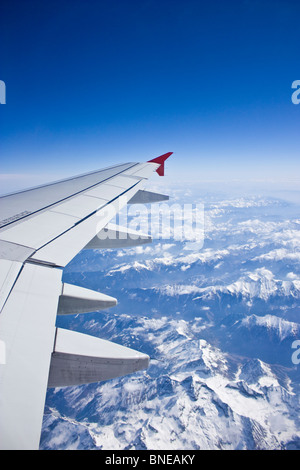 Flying over the alps, snow capped mountains, view of airplane wing - Stock Photo