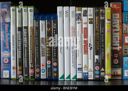 row of dvd vhs blu-ray video cases and wii and xbox360 video games on a shelf in the uk - Stock Photo