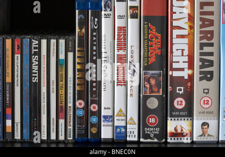 row of dvd vhs blu-ray video cases and cd albums on a shelf in the uk - Stock Photo