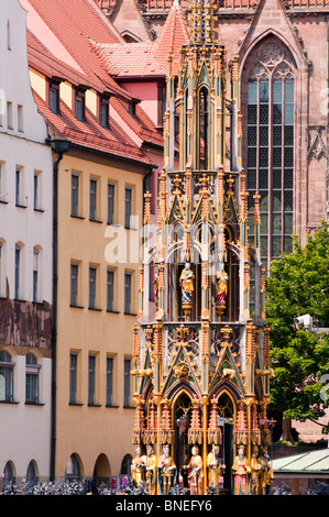 Schoner Brunnen fountain together with shop facades and church. Seen from Hauptmarkt in Nuremburg, Germany. - Stock Photo