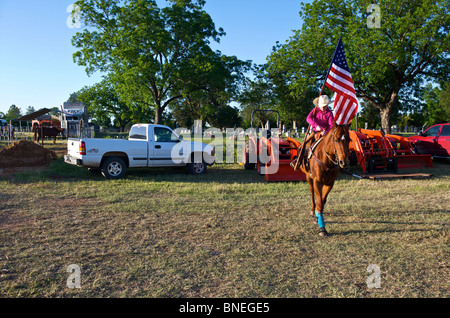 Cowgirl  waving flag in stockyard before opening ceremony of PRCA rodeo event in Texas, USA