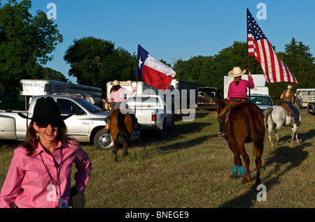 Cowgirls waving flag in stockyard on opening ceremony of PRCA rodeo event in Texas, USA - Stock Photo