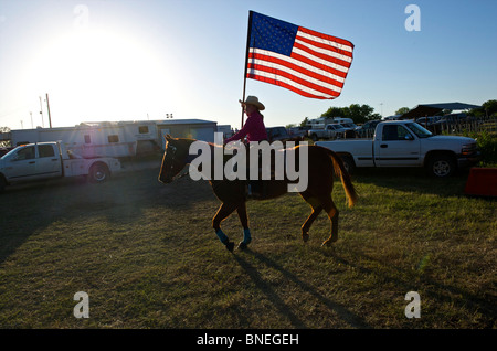 Cowgirl waving American flag at opening ceremony of PRCA rodeo event in Texas, USA