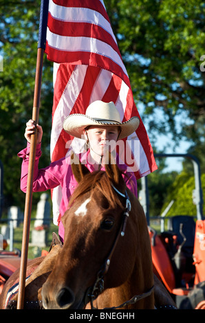 Cowgirl waving American flag  at PRCA rodeo event in Texas, USA