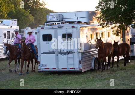 Cowboy members of PRCA riding horses backstage at rodeo event in Bridgeport Texas, USA - Stock Photo