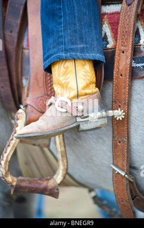 Boots and spurs of cowboy riding horse - Stock Photo