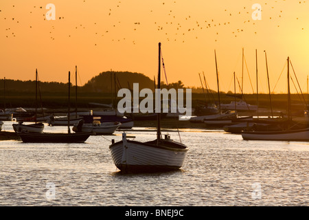 The sun setting behind boats moored on the River Burn at Burnham Overy Staithe - Stock Photo