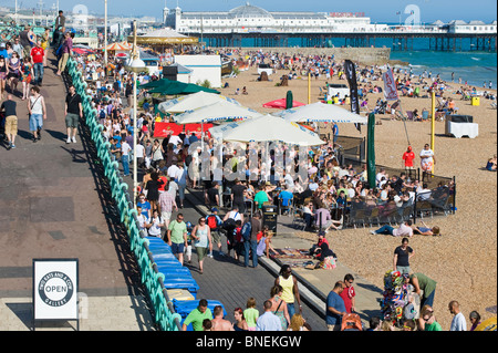 Crowded seafront and pebble beach, Brighton, East Sussex, United Kingdom - Stock Photo