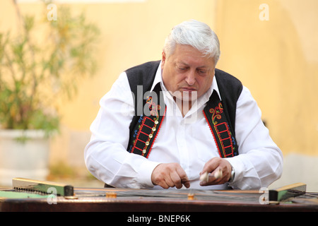 Senior gypsy musician playing the cymbalo during the official preview of Mr. Fedor Malik's new book - Camembert - Stock Photo