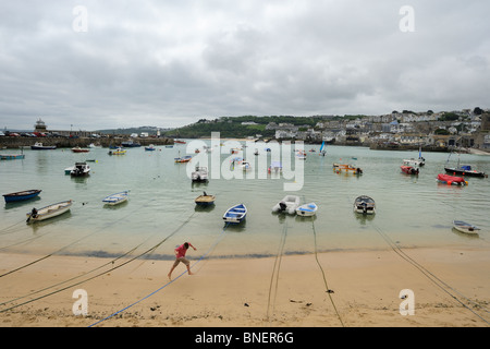 A boy hops over mooring ropes in St Ives Harbour - Stock Photo