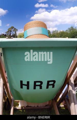 Woman wearing a straw hat sitting in a deckchair at Henley Regatta - Stock Photo