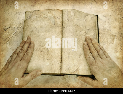 Hands and open book on grunge image - Stock Photo
