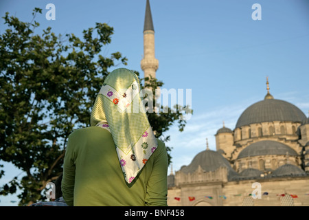 Back of Turkish girl in headscarf and the New Mosque, Istanbul, Turkey - Stock Photo