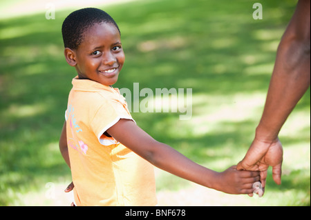 Portrait of girl (8-9) holding fathers hand, Johannesburg, Gauteng Province, South Africa - Stock Photo