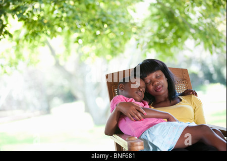 Mother sleeping with daughter (8-9) in garden chair, Johannesburg, Gauteng Province, South Africa - Stock Photo