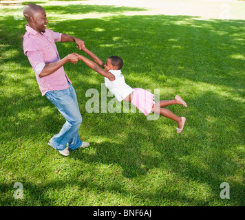 Father swinging daughter (8-9) on lawn in garden, Johannesburg, Gauteng Province, South Africa - Stock Photo