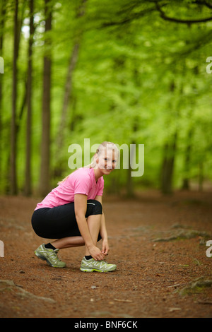 Woman running, tying laces - Stock Photo
